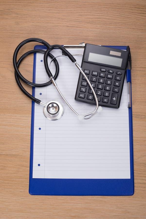 金属stethescope和计算器在笔记本 免版税库存照片