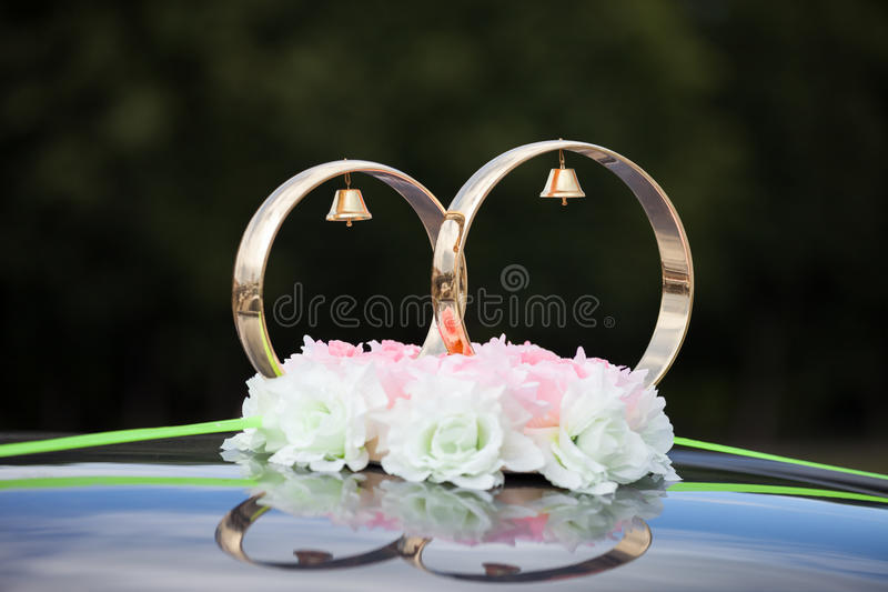 金戒指和玫瑰色花在婚礼汽车 库存照片