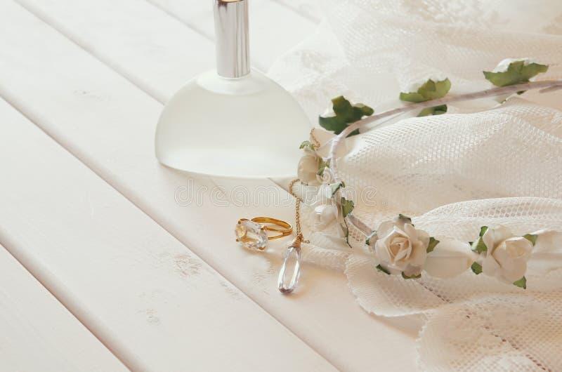 金戒指和项链、白色花卉冠状头饰和香水瓶 免版税库存照片