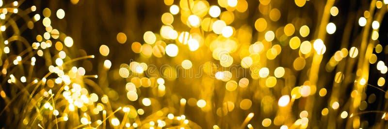 金抽象bokeh背景圣诞节背景 与bokeh defocused光和星的欢乐抽象背景 免版税库存照片