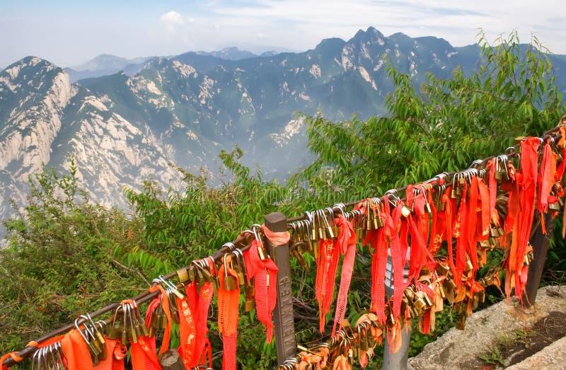 金挂锁和红色丝带在神圣的华山山 免版税库存图片