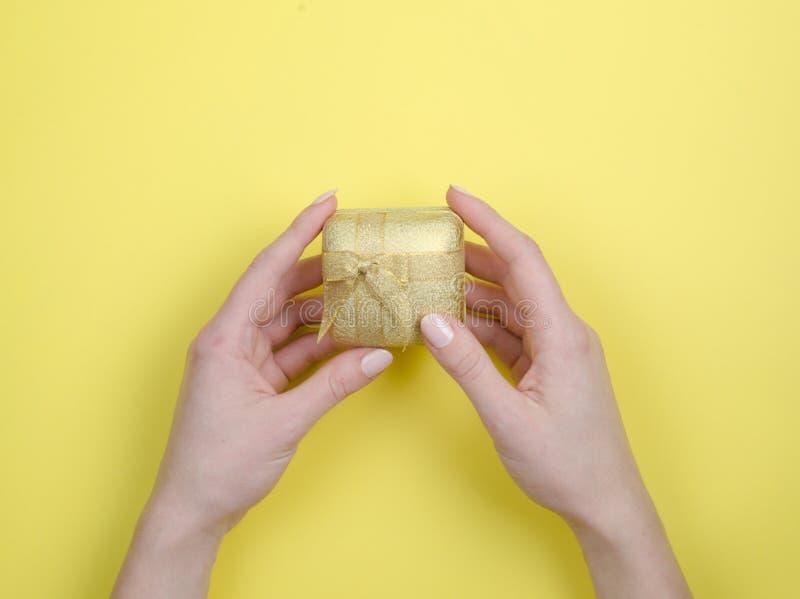 金有弓的礼物盒在手中在黄色背景 免版税库存照片