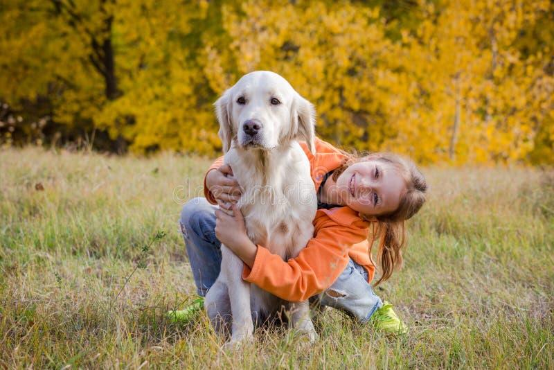 金毛猎犬坐与女孩的领域 免版税库存照片