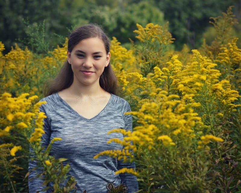 金毛茛花的领域的青少年的女孩 免版税库存照片