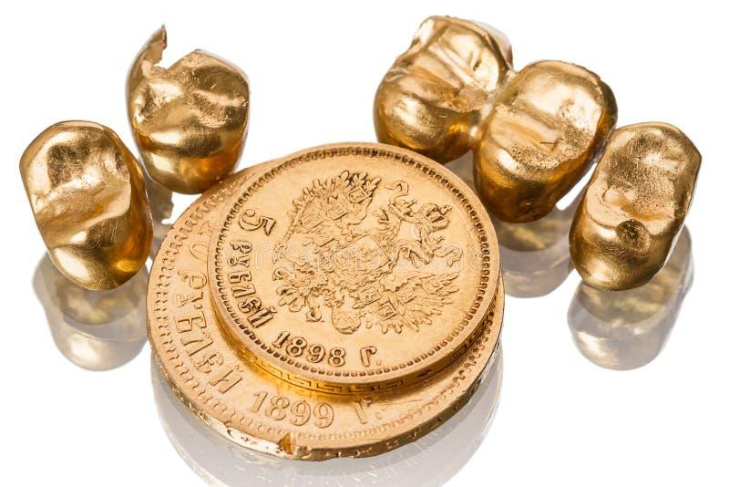 金牙齿冠和老硬币 库存照片
