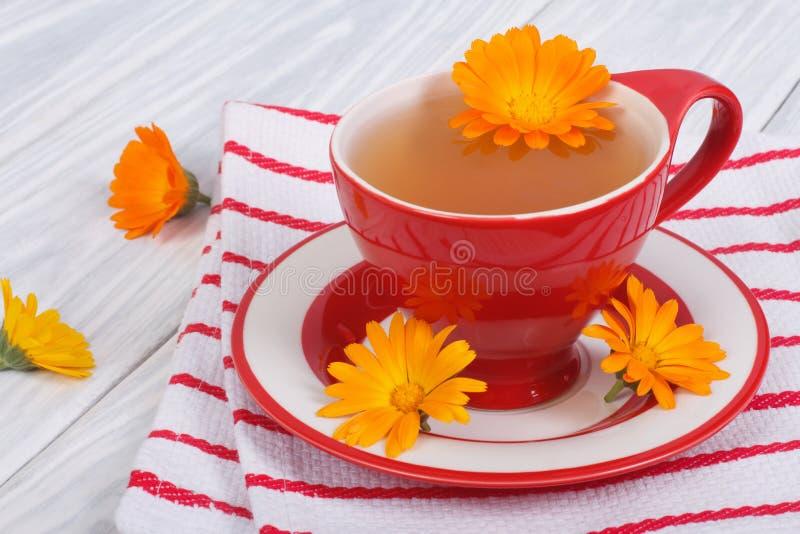 金盏草在镶边桌布的花茶 免版税库存图片