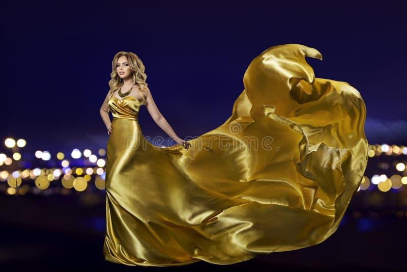 金礼服的妇女在夜城市,在长的金黄褂子,挥动的织品的时装模特儿 免版税图库摄影