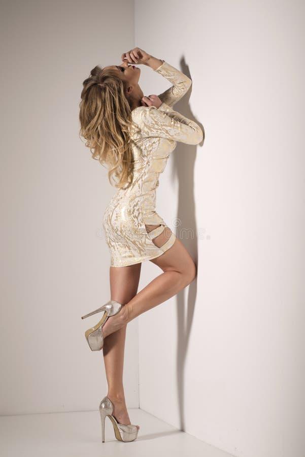 金礼服的性感的白肤金发的夫人 免版税图库摄影