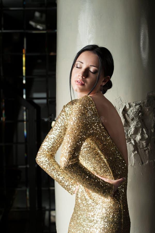 金礼服的美丽和性感的妇女 免版税库存图片