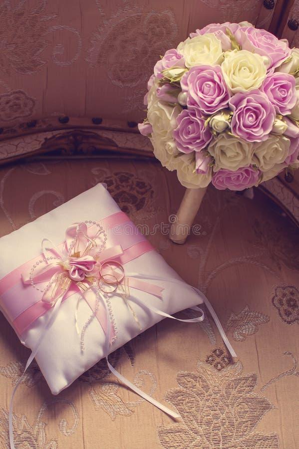 金结婚戒指在有桃红色缎带的一个装饰丝绸枕头说谎在新娘的花束旁边 定调子与样式  图库摄影