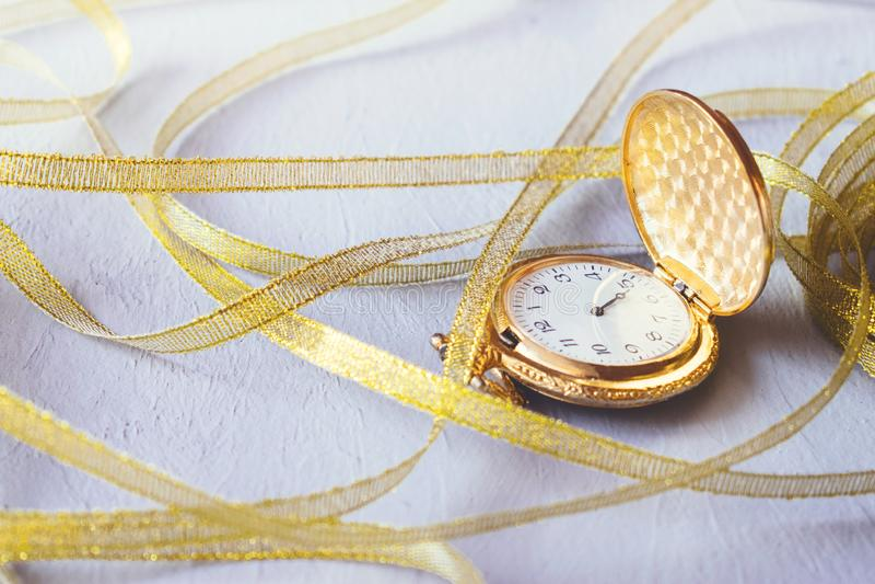 金葡萄酒有金黄丝带的怀表在灰色水泥背景 滴漏或沙子定时器,时间的标志 选择聚焦 免版税库存照片