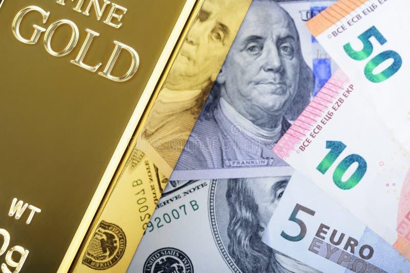 金金属在美元和欧元票据背景的锭金块  库存照片