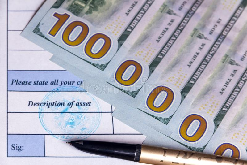 金钢笔在财产描述文件说谎 一百万美元从五百美金当中 Bitcoin蓝色邮票 免版税图库摄影