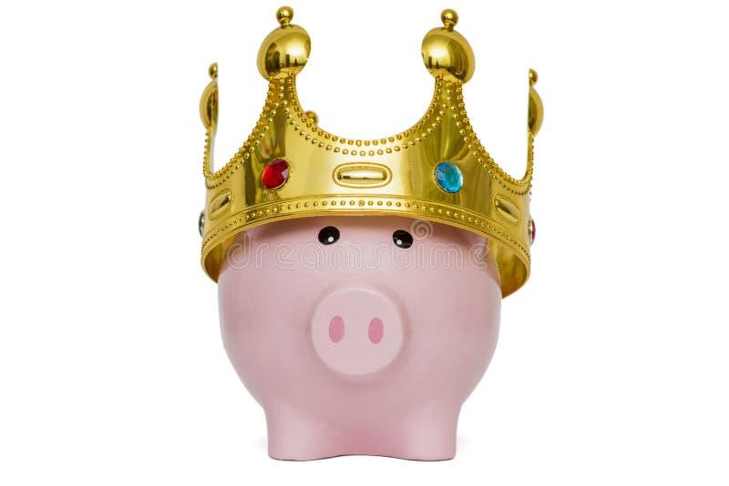 金钱储款概念的财政优胜者或国王,佩带在上面的桃红色存钱罐一个金黄冠在白色背景,最佳的未来 免版税图库摄影