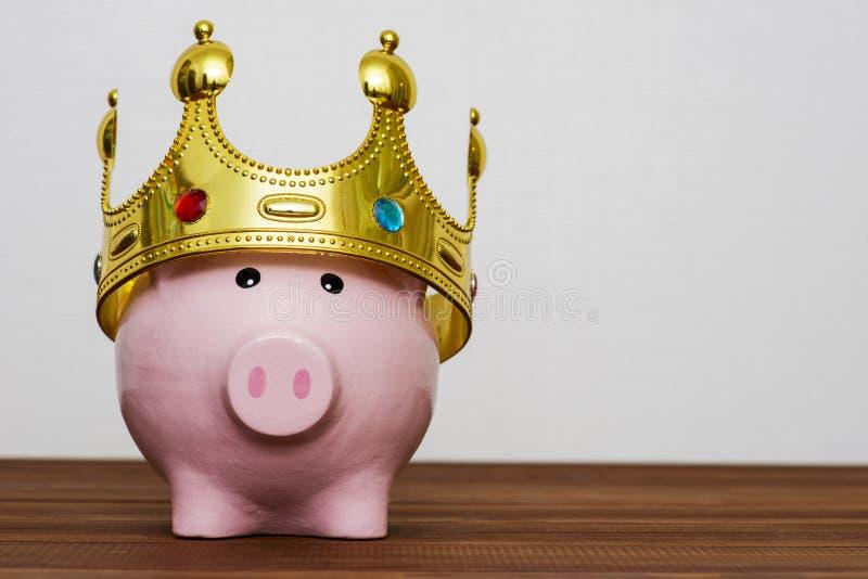 金钱储款概念的财政优胜者或国王,佩带在木桌,最佳的futu上的微笑的愉快的桃红色存钱罐一个金黄冠 免版税图库摄影