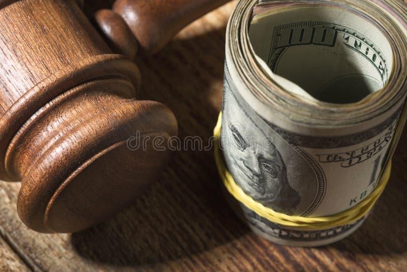 金钱卷和法官在木桌上锤击 免版税库存图片