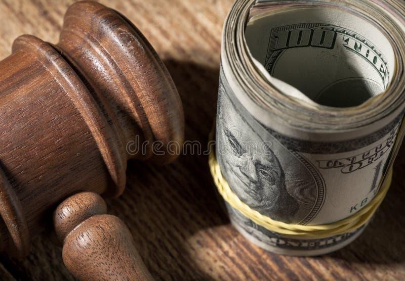 金钱卷和法官在木桌关闭锤击  图库摄影