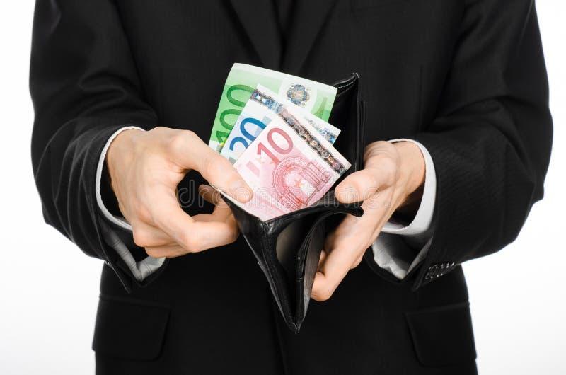 金钱和企业题材:拿着有纸币欧元的一套黑衣服的一个人一个钱包隔绝在白色背景在演播室 库存照片