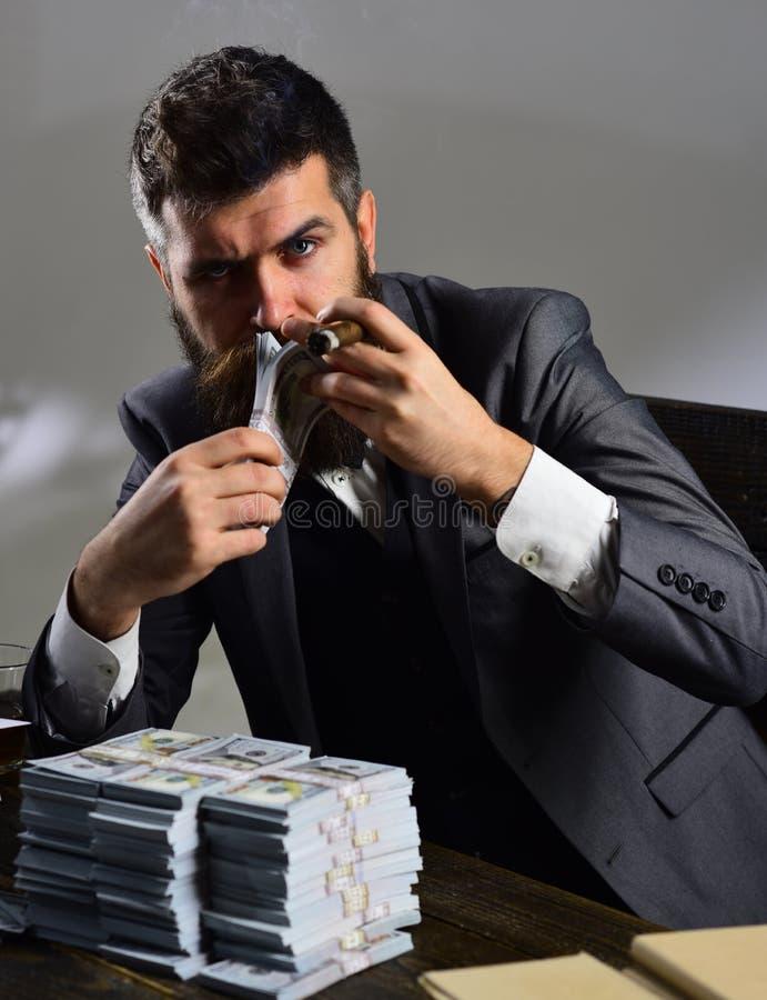 金钱和力量 商业和财务 有胡子的人计数美元,当抽雪茄时 成功的商人举行现金 免版税库存图片