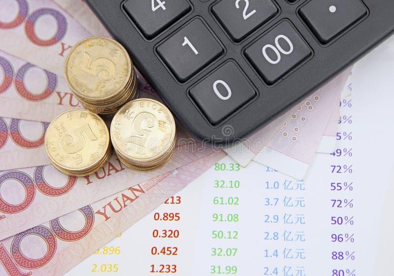 金钱和计算器在书桌上有图的 免版税库存照片