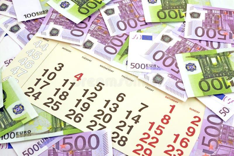 金钱和计算器在月日历 免版税库存照片