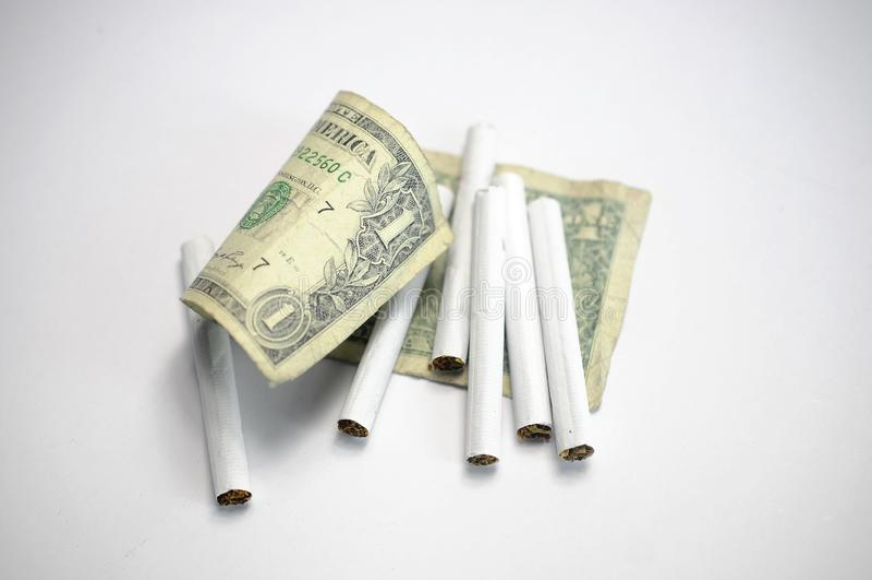 金钱和香烟在白色背景 免版税库存图片