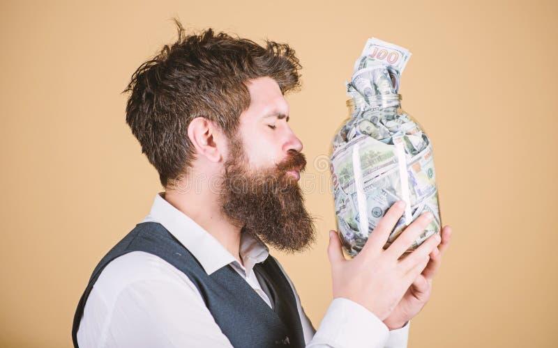 金钱恋人 残酷有金钱的商人亲吻的玻璃瓶子 有胡子的人保存的现金金钱在存钱罐中 他是贪婪的 免版税库存图片