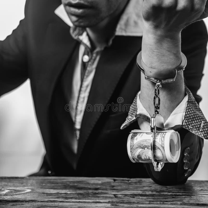 金钱概念奴隶  商人的手被绑住到美国玩偶 图库摄影