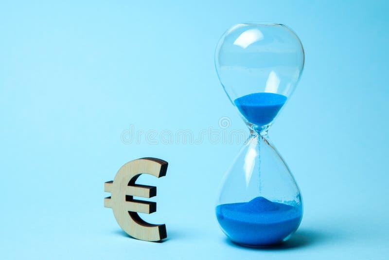 金钱欧元的滴漏和标志在蓝色背景的 库存照片