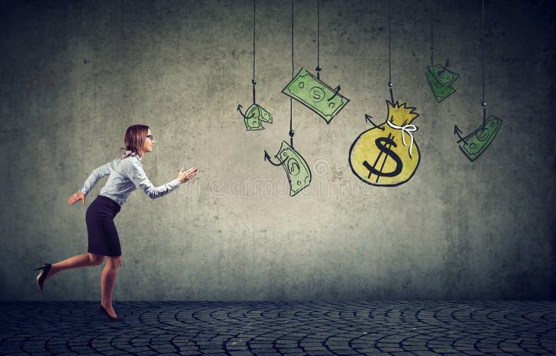 金钱激发的女商人垂悬在一个钓鱼钩 现金美元的女实业家赛跑 免版税库存照片