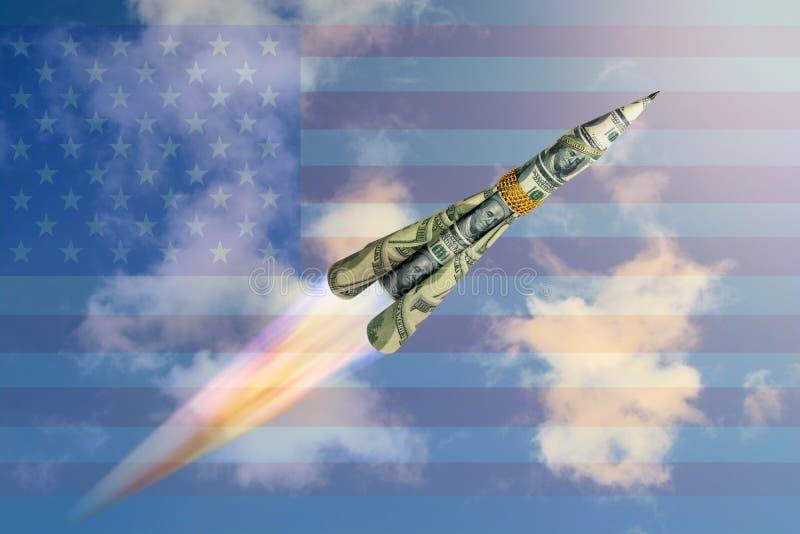 金钱火箭上升入天空反对美国国旗的背景 免版税库存图片