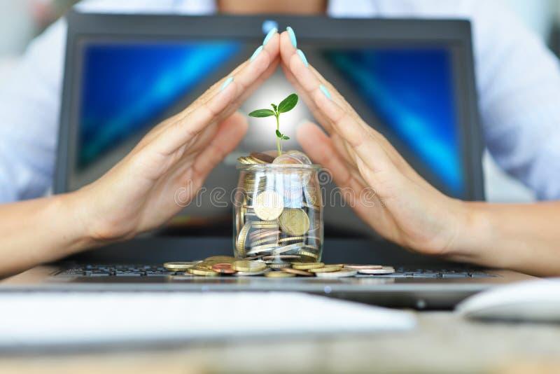 金钱的保护免受网上交易概念,当woman's手包括一个瓶子在笔记本上的硬币 免版税库存图片