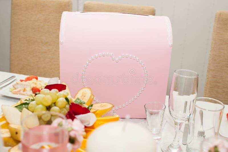 金钱的婚礼箱子与以心脏的形式一个样式 背景钮扣眼上插的花看板卡装饰装饰邀请婚姻白色的珍珠玫瑰 免版税库存图片
