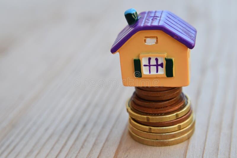 金钱硬币堆的五颜六色的房子 库存照片