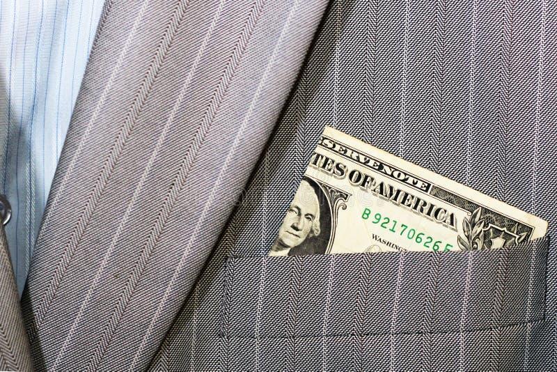 金钱美国美元堆被困住在军用卡其色的外套或袋子口袋外面有美国国旗补丁的 免版税库存图片