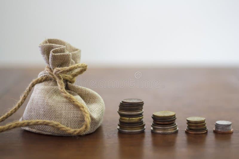金钱袋子和硬币堆在一张木桌上 库存照片