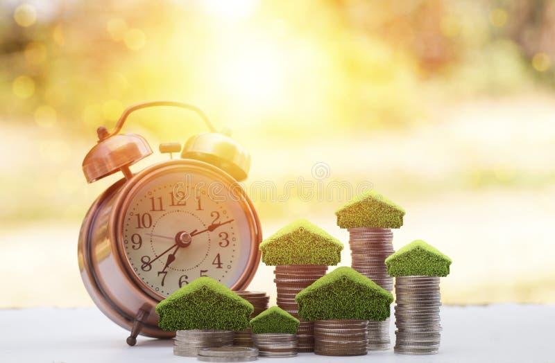 金钱被堆积硬币为房子、小树和家保存在与闹钟的堆在木桌有阳光背景, 库存图片