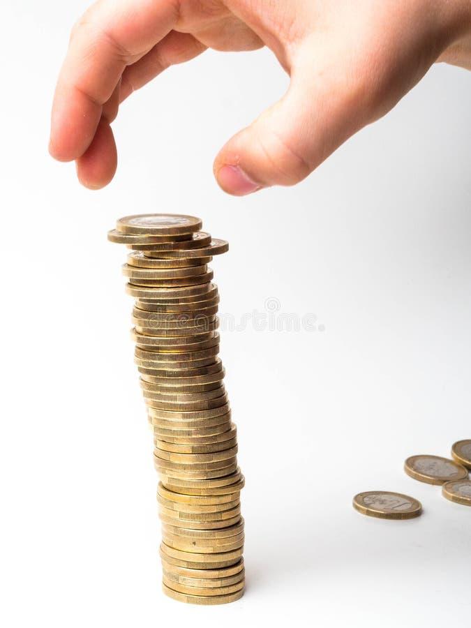 金钱,财政,企业成长概念,人的手投入硬币堆积在白色背景的硬币 库存照片