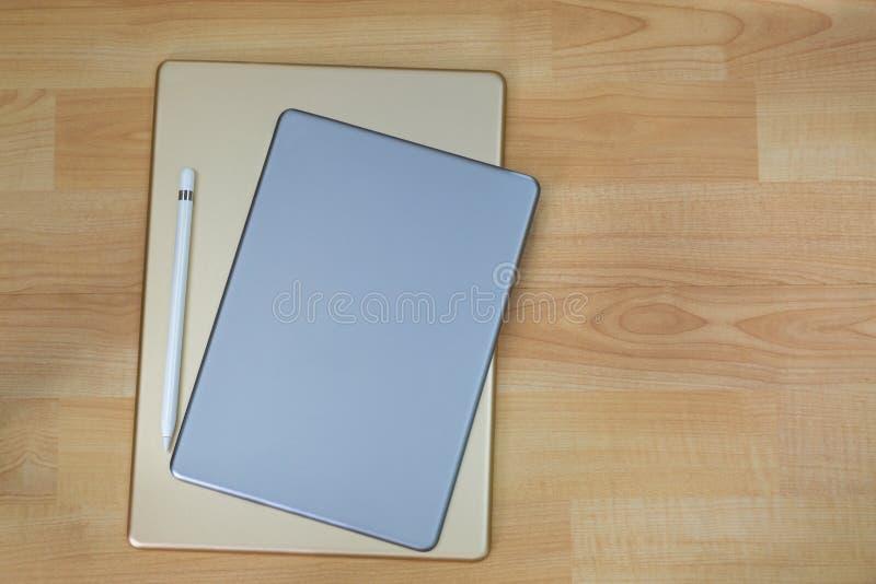 金银赞成片剂计算机后侧方在白色铅笔旁边的 免版税库存图片