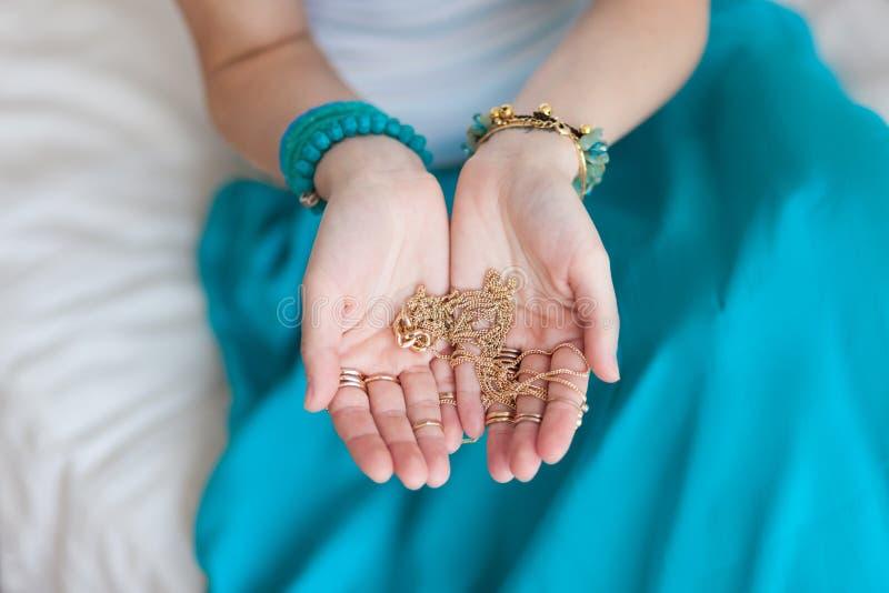 金链子在一名年轻可爱的东方妇女的手上 库存照片
