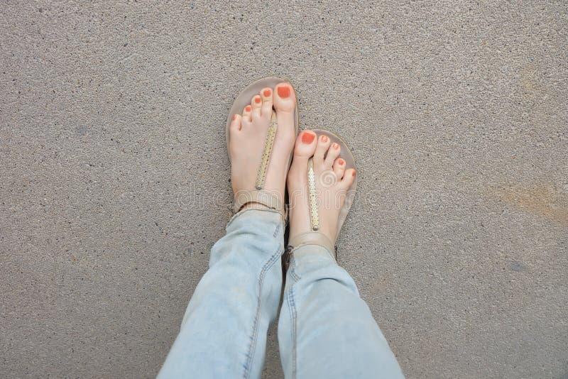 金鞋子& x28; Slippers& x29;在女孩腿和脚在地面上 库存图片