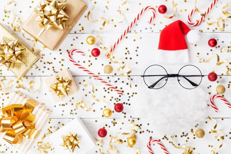 金黄五彩纸屑、礼物或者当前箱子和滑稽的圣诞老人圣诞节背景在白色台式视图 平的位置 免版税库存照片