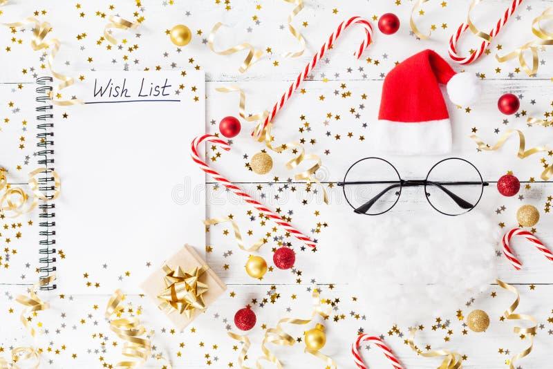 金黄五彩纸屑圣诞节背景、礼物或者当前箱子、愿望笔记本和滑稽的圣诞老人在台式视图 平的位置 库存照片