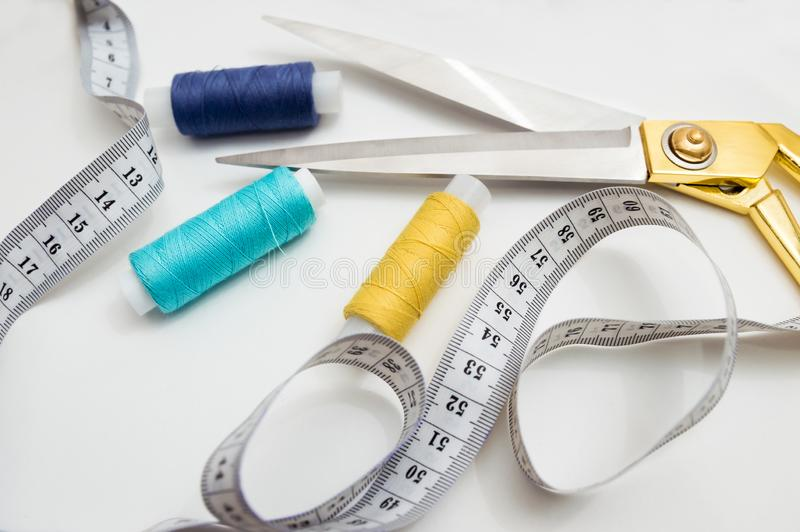 金黄剪刀、蓝色,蓝色和黄色螺纹、测量的磁带说谎在白色背景的,切开的一个集合和缝合 免版税库存照片