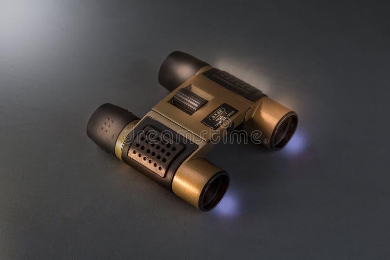 金黄口袋双筒望远镜,在灰色背景的黑暗的光 向量例证