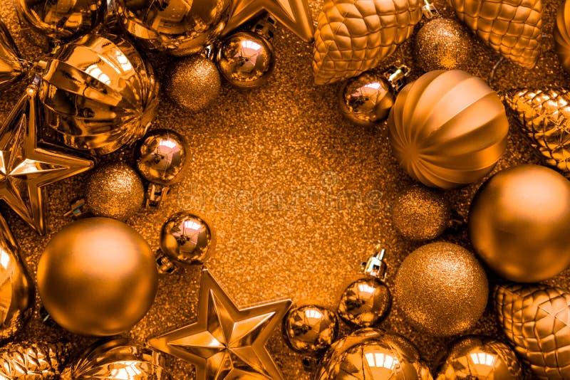 金黄圣诞节的框架 圣诞节球、星、锥体和心脏在金黄闪闪发光背景 平的位置 顶视图 复制空间 图库摄影