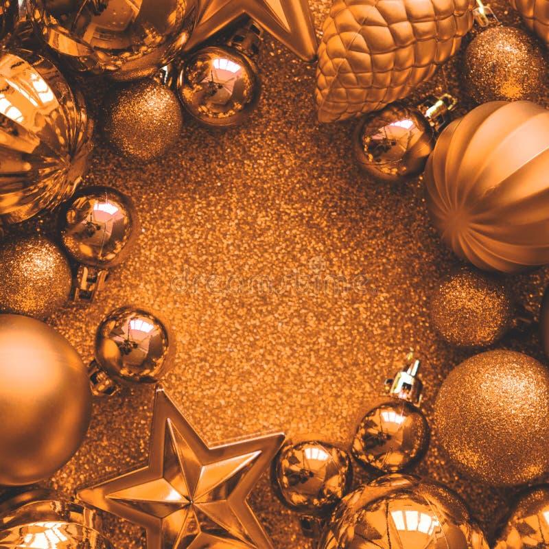 金黄圣诞节的框架 圣诞节球、星、锥体和心脏在金黄闪闪发光背景 平的位置 顶视图 复制空间 免版税库存图片