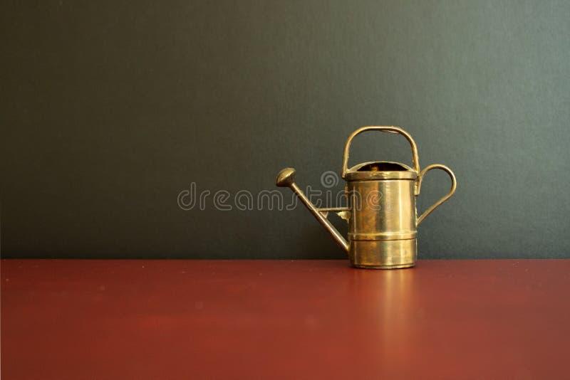 金黄在黑背景前面的葡萄酒微型喷壶 免版税库存照片