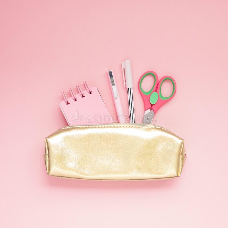 金黄女孩学校盒顶视图平的位置与办公用品的有最小拷贝空间千福年的粉色纸的背景 图库摄影