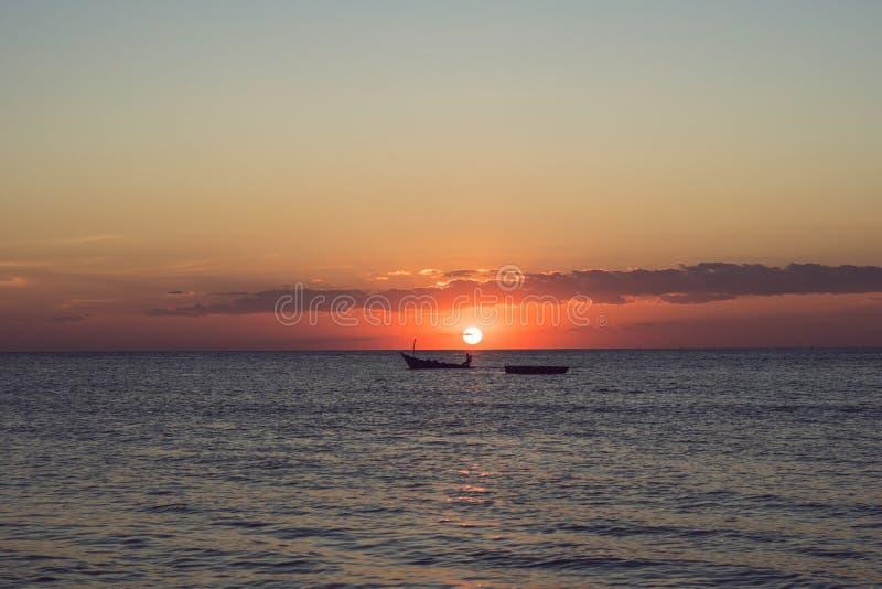 金黄日落到有海岛的剪影的海里 库存图片